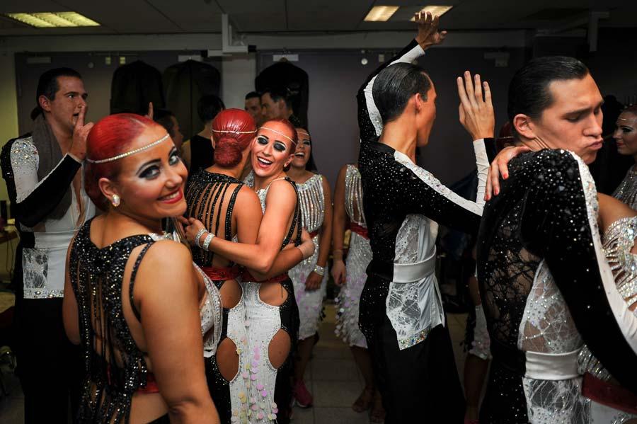 Tänzerinnen und Tänzer des TSV Buchholz stehen in einer Umkleidekabine und lächeln mit den Augen und mit den Lippen. Sie tragen nach wie vor ihre Tanzkleidung - funkelnde Kleider die Frauen und Ganzkörperanzüge die Männer. Eine Frau mit dunkelrot gefärbten Haaren steht mit dem Rücken zur Kamera, hat aber den Kopf zum Fotografen gedreht und lächelt, während sich vor ihr eine Tänzerin und ein Tänzer umarmen. Sie freuen sich bei ihrer ersten Teilnahme an den deutschen Meisterschaften der Formationen Standard und Latein alle über ihren fünften Platz.