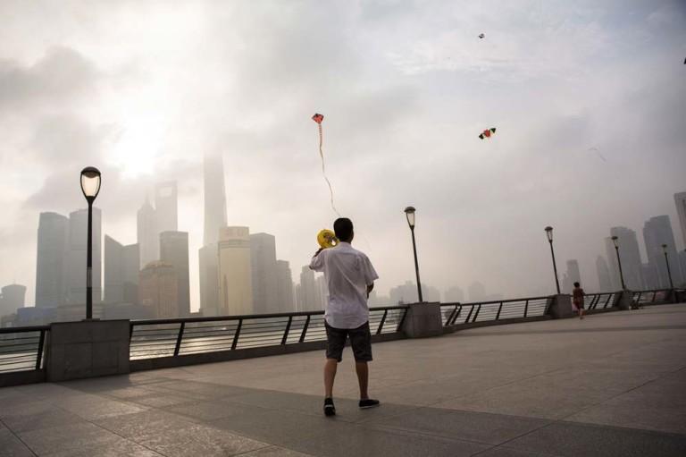 Einheimische lassen an der Uferpromenade The Bund in Shanghai ihre Drachen steigen. Im Hintergrund ragen Hochhäuser in den Morgennebel. Foto: Manuel Hauptmannl