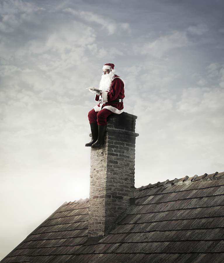 Der Weihnachtsmann sitzt auf einem Schornstein und schaut in ein Tablet. Darauf liest er unseren Editorial-Blog und blickt zurück auf Artikel aus dem vergangenen Jahr.
